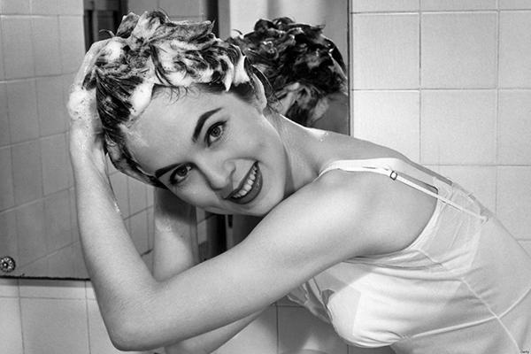 Woman washing hair in bathroom sink