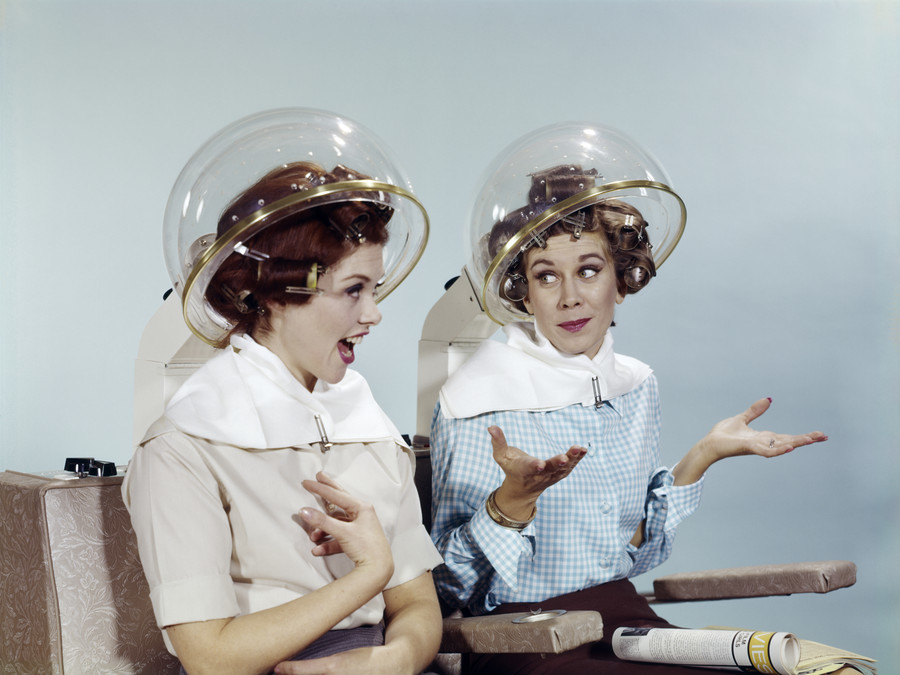 1960s 2 WOMEN SIT UNDER BEAUTY SALON HAIR DRYERS CLEAR HELMETS HOODS CURLERS TALKING GOSSIP  (Photo by H. Armstrong Roberts/ClassicStock/Getty Images)