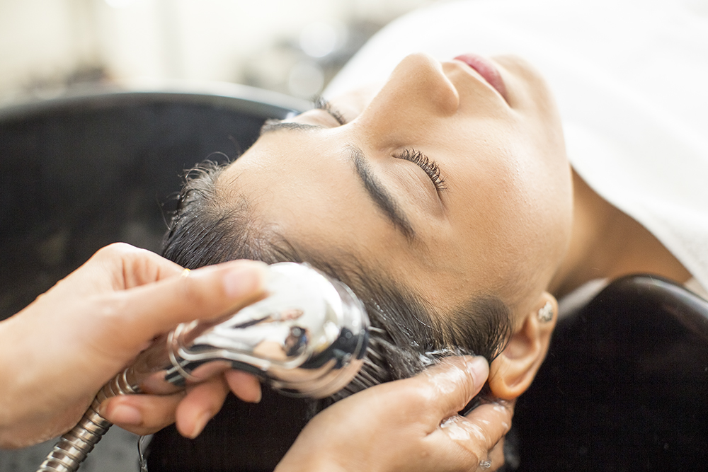 Close-up of face of relaxed young Latin American woman with closed eyes sitting at hair salon. Hands of hairdresser washing her face with shower