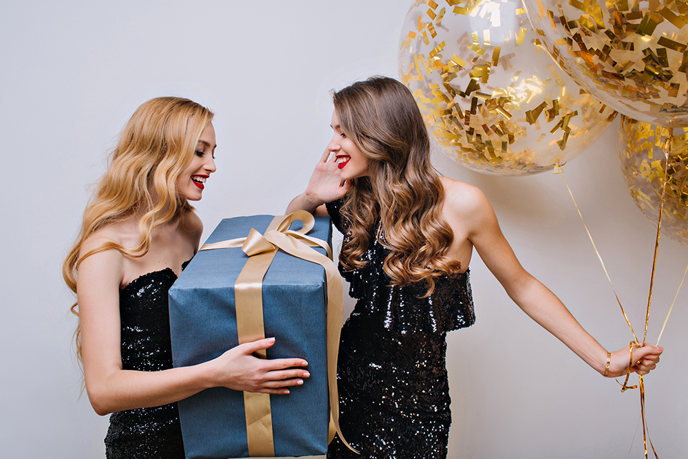 Amazing blonde girl received big present from female friend with light-brown hair. Indoor portrait of charming young woman holding gift for brunette sister which holding party balloons.
